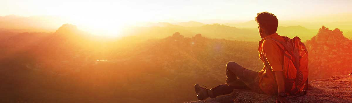 man with backpack watching sun set over mountains